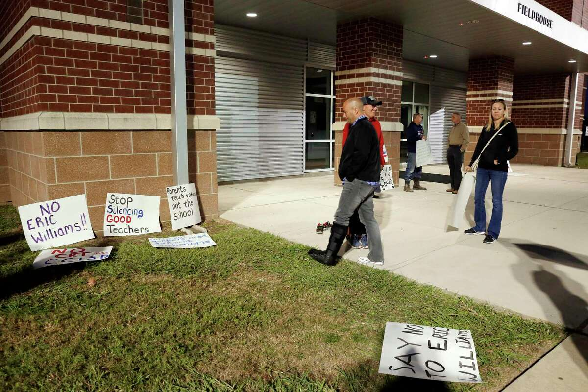 Parents and community members, protesting the choice of Eric Williams as new superintendent, pick up pre-made signs outside of the Clear Creek ISD board meeting, moved from the district headquarters to six miles away at the Challenger Stadium Fieldhouse Monday, Nov. 16, 2020 in Webster, TX.