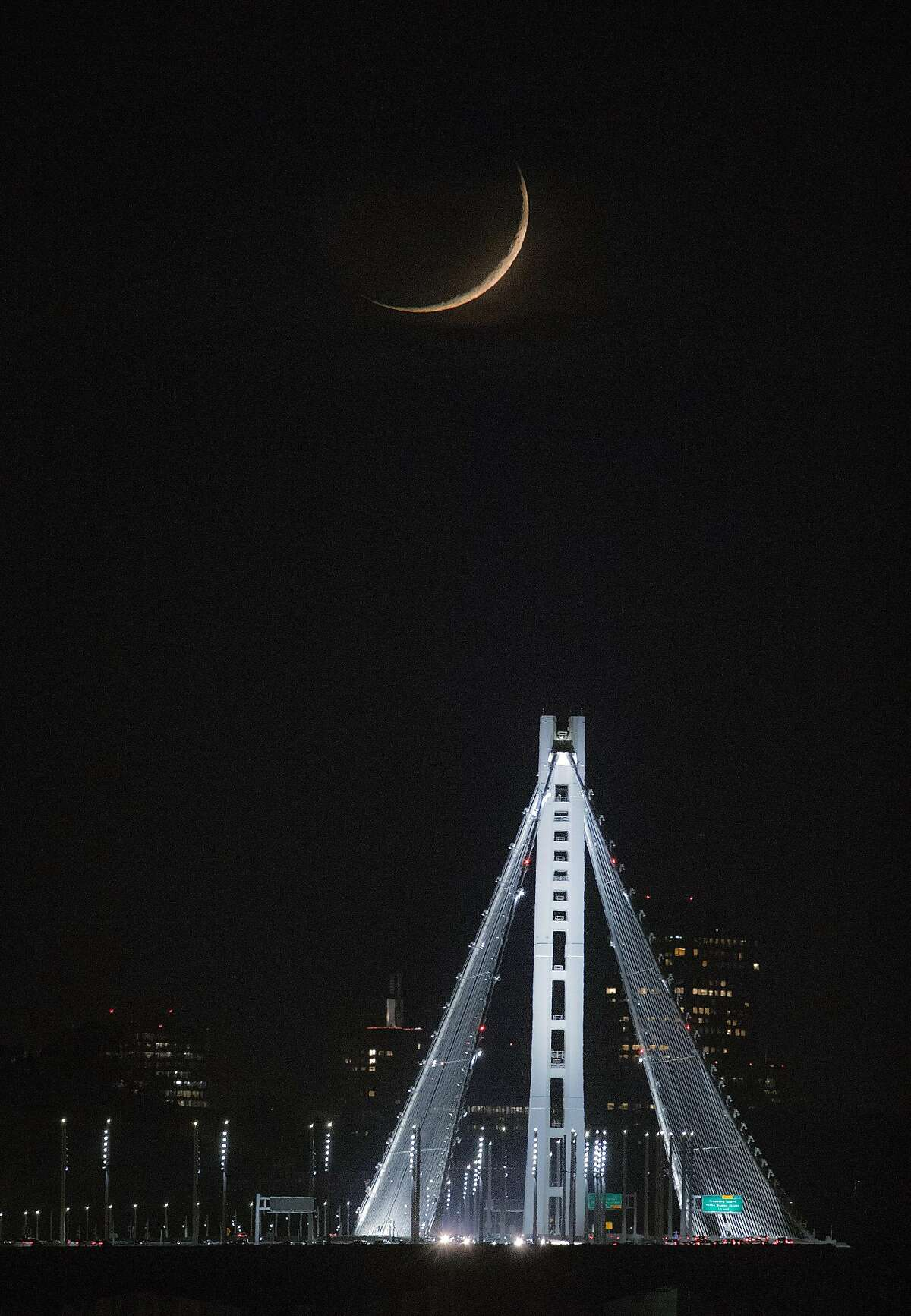 The waxing crescent moon appears through thin clouds over the eastern span of the Bay Bridge as seen from Emeryville, Calif., on Monday, November 16, 2020. Clouds were building up along the coast as rain is predicted for Tuesday.