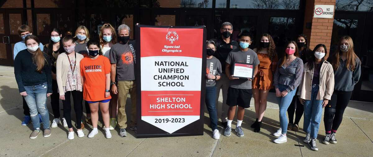 Shelton High School was honored by Special Olympics through the CIAC with a National Unified Champion School banner on November 6, 2020. Holding the banner are unified coaches Mike Gambardella (left) and Karen Devonshuk (right) with Shelton High School athletic director John Niski (next to Devonshuk) and unified athletes.