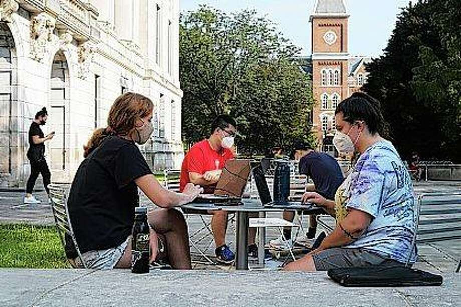 Students Jessica DeSena (right) and Camden Coggburn (left), both of Columbus, sit outside Thompson Library during the first day of fall classes at Ohio State University in Columbus, Ohio. Colleges in the U.S. have seen a sharp enrollment drop among international students this fall. University administrators say a number of hurdles and new policies brought on by the coronavirus pandemic are to blame. Photo: Joshua A. Bickel | The Columbus Dispatch Via AP