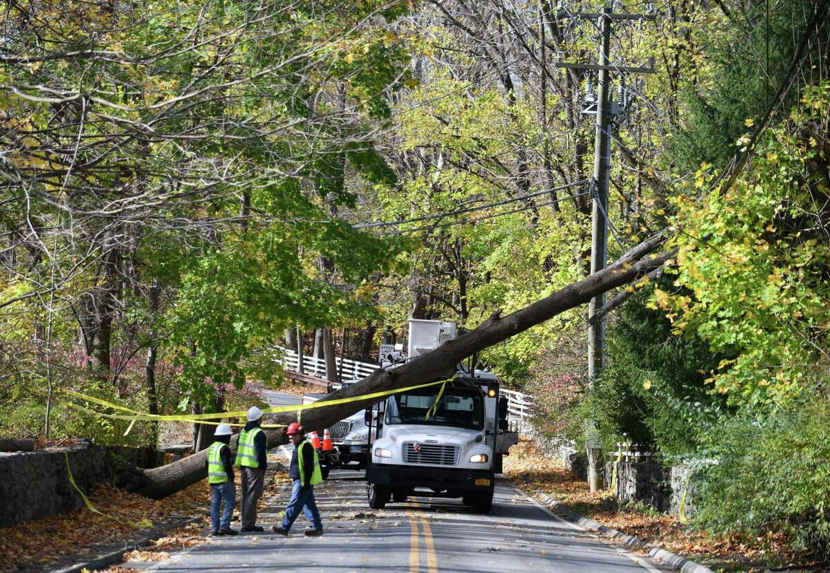 Crews clear a downed tree perched atop power lines on Lower Cross Road in Greenwich, Conn., on Monday, Nov. 16, 2020. Wind gusts from Sunday's storm exceeded 70 mph, downing trees throughout town.