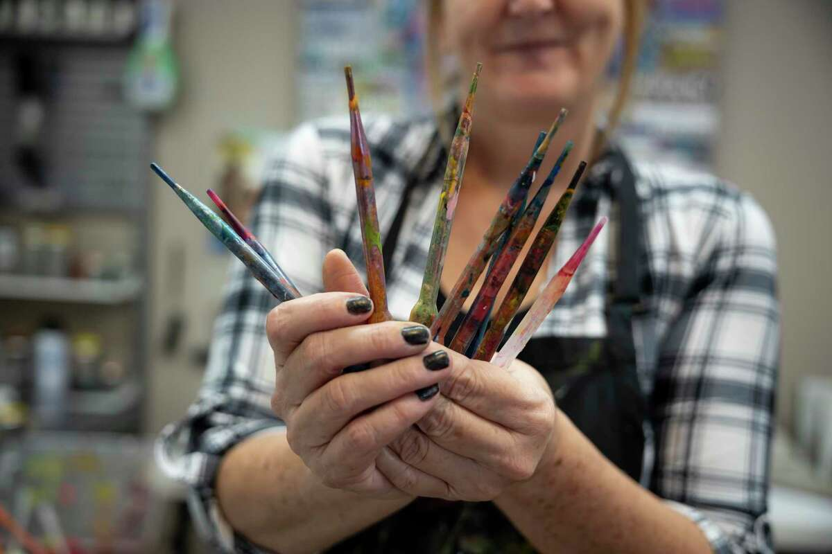 Toria Hill holds her favorite painting instrument, pipettes, in her studio at her home, Thursday, Nov. 12, 2020, in Willis. Hill plans to showcase at least 20 pieces for a show in 2021.