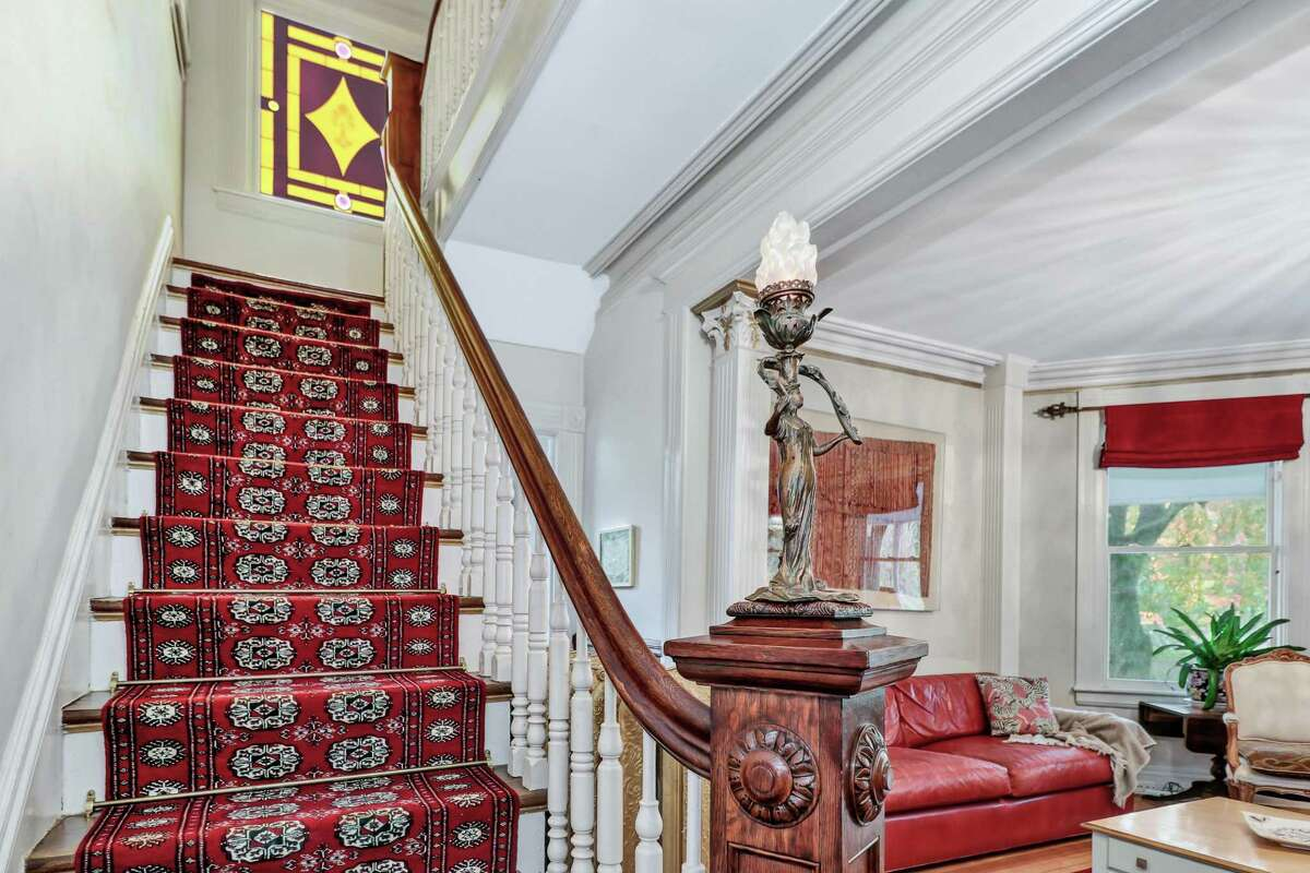 A hand-carved decorative newel post is topped with a period art nouveau lantern that was originally gas-fueled, but was converted to electric. The nine-room, 2,749-square-foot house sits on a 0.19-acre level property in the Stratfield neighborhood, across the street from the Brooklawn Country Club golf course. The driveway of this corner lot is on Querida Street, and it provides off-street parking as well as a detached two-car garage with a separate entrance to a storage loft. That loft can be finished to create more living space; perhaps a home office, an art or yoga studio, or a game room.