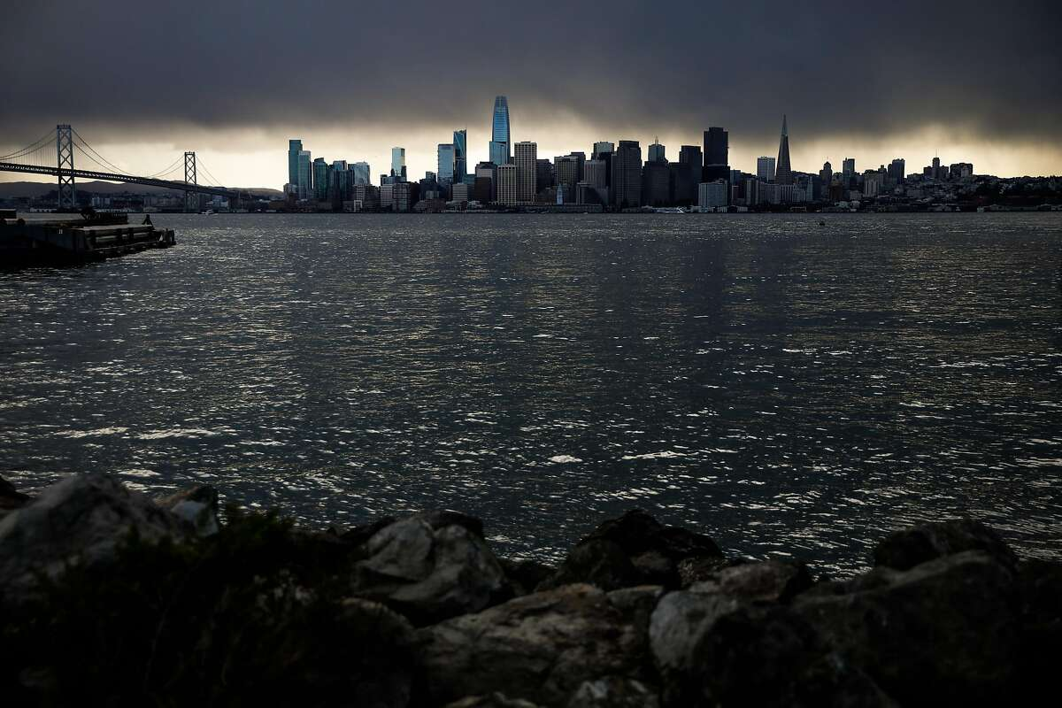 The San Francisco skyline is seen covered in dark clouds during a rainstorm at Treasure Island on Sunday, Nov. 8, 2020 in San Francisco, California. A cold front bringing light to moderate rains is still expected to sweep over the Bay Area Nov. 17, with San Francisco on tap to receive up to half an inch of precipitation beginning in the afternoon.