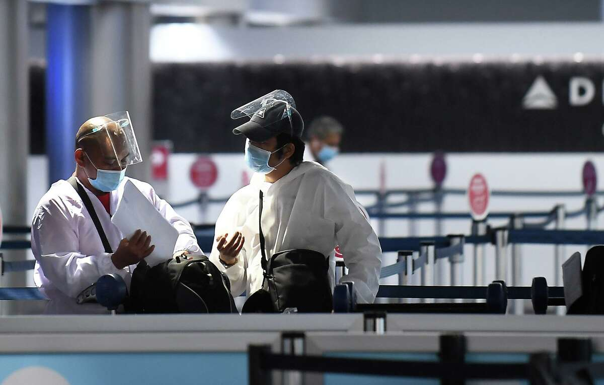 Travelers wearing full body suits and masks prepare to head to their gate in Terminal 2 at Los Angeles International Airport on November 13, 2020. Some airports, including Atlanta's and Sioux Fall, South Dakota's, don't have mask mandates in place. (Wally Skalij/Los Angeles Times/TNS)