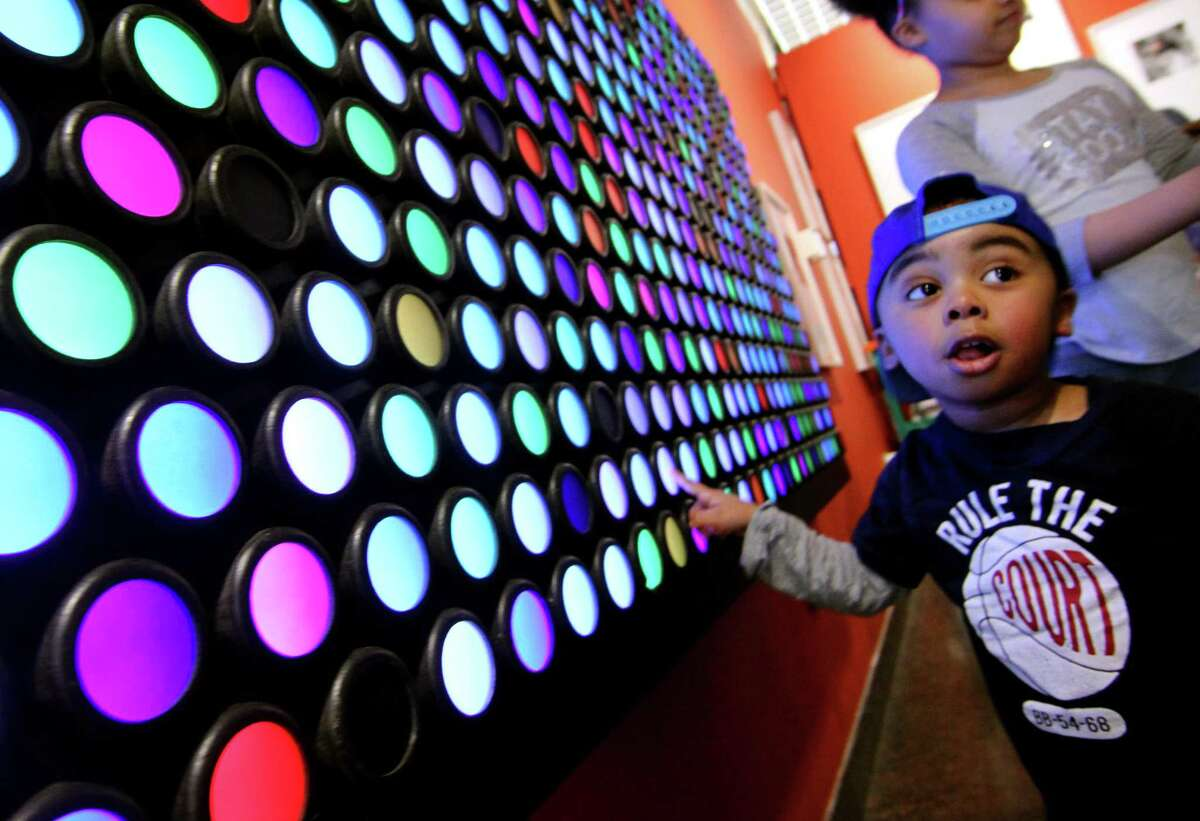 Ahsaan Carswell, 2, enjoys changing the colors on light cells mounted on a wall during the Discovery Museum's annual Science Day in Bridgeport, Conn., on Saturday April 6, 2019.