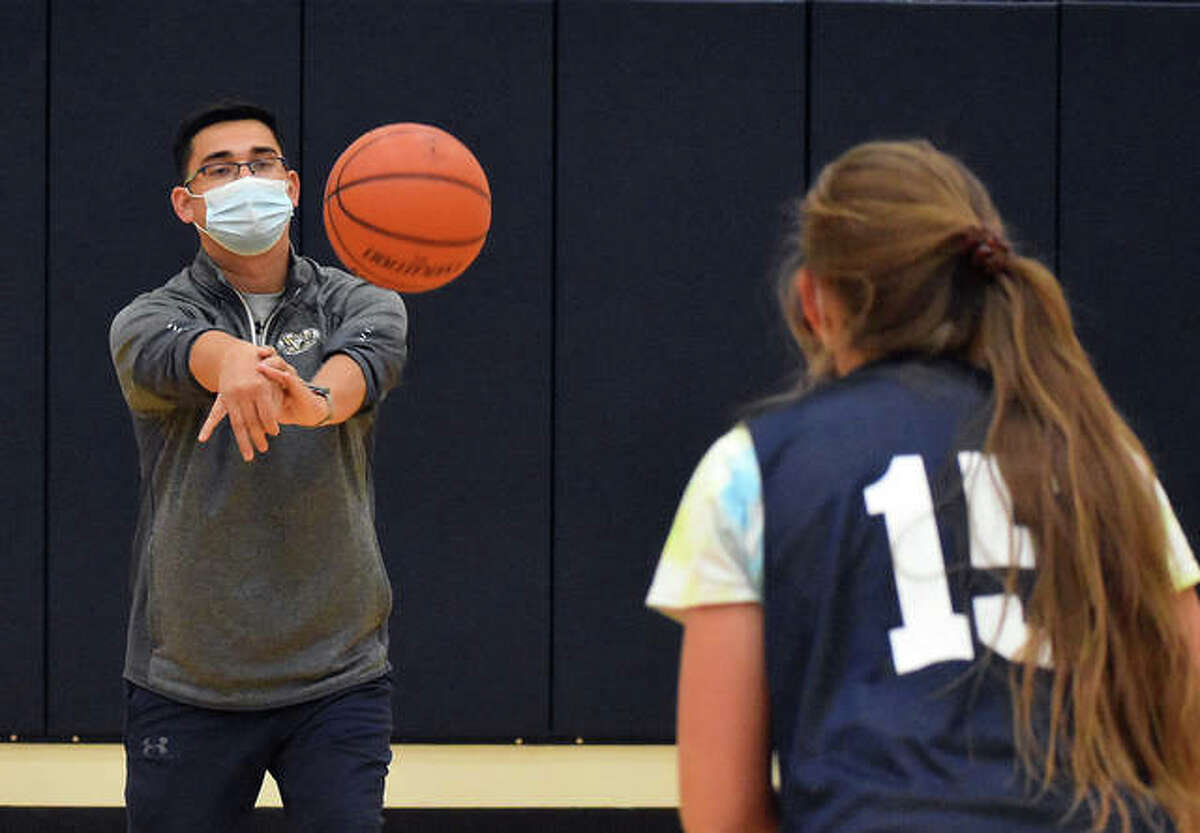 Father McGivney coach Jeff Oller delivers a pass to Grace Stanhaus during a shooting drill Monday.