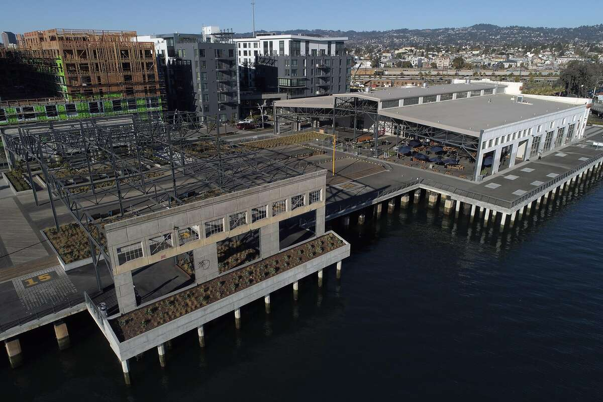 An aerial view of the eastern half of Township Commons, a 4.5-acre park that includes remnants of the shipping terminal that once filled the wharf along the Oakland Estuary. In the background is new housing that marks the initial phase of Brooklyn Basin in Oakland. Township Commons is the 65-acre project's first public space.