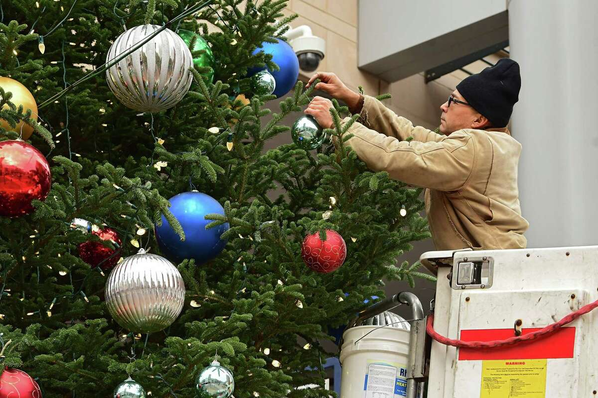 Transfinder employee John Daniels is seen in a bucket truck decorating a Christmas Tree on the corner of State and Jay Streets on Tuesday, Nov. 17, 2020 in Schenectady, N.Y. Transfinder, which is located across the way on State St., sponsors the holiday tree. (Lori Van Buren/Times Union)