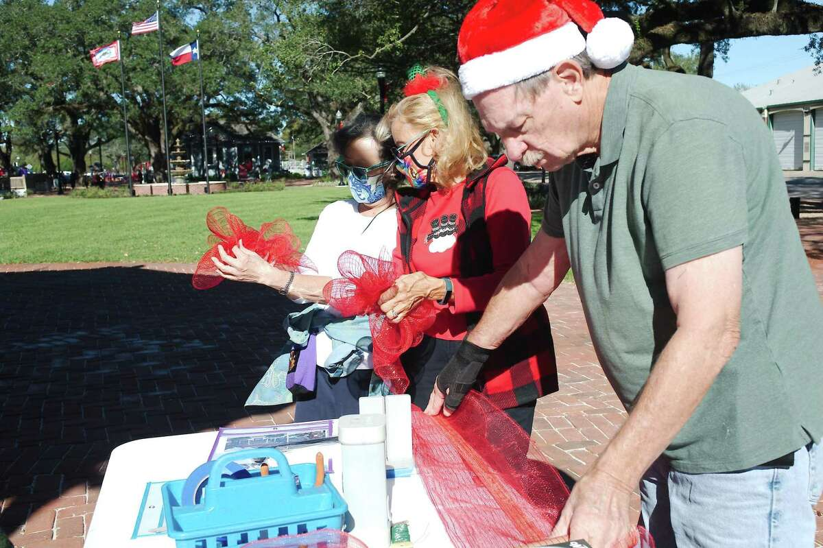 League City Garden Club volunteers Leslie Wong, Sherry Nuzzi and Bob Blackwell tie bows to be hung with other decorations on the bandstand.
