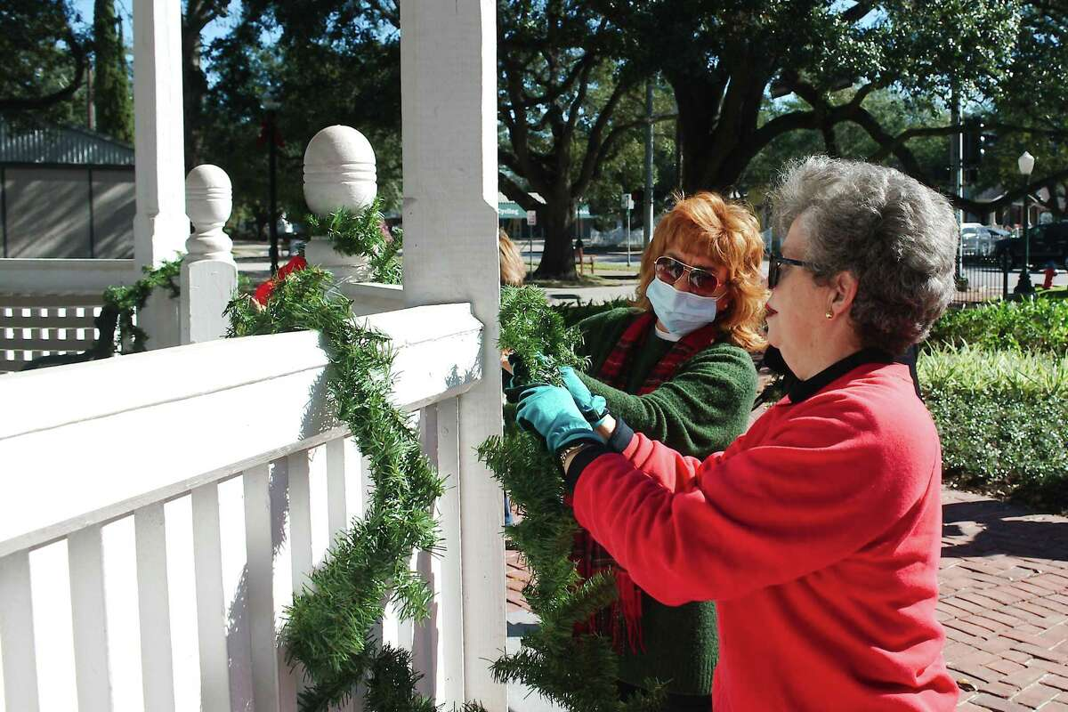 League City Garden Club members Judith Muller and Judith Taub hang decorations on the bandstand.