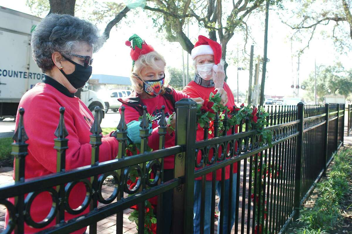 League City Garden Club volunteers Judith Muller, Sherry Nuzzi and Tauni Bryan hang decorations in League Park.