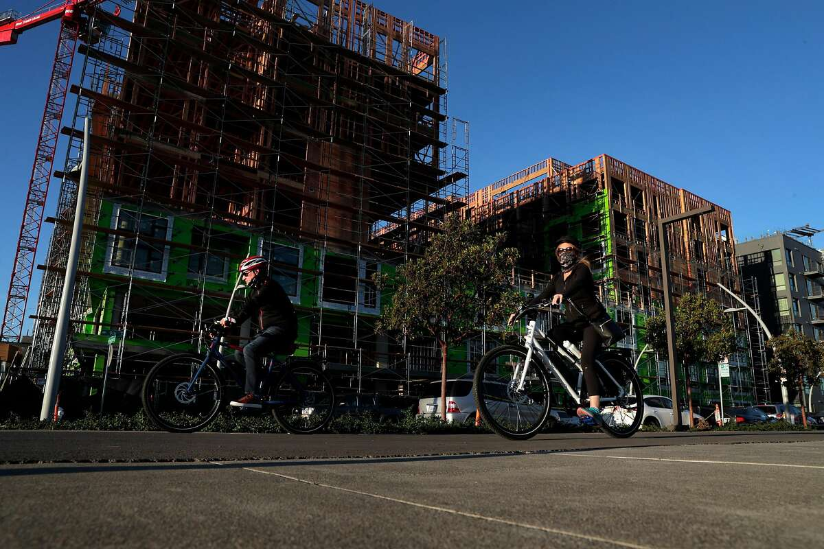 Bicyclists ride along Ninth Avenue in the Brooklyn Basin development along the estuary in Oakland, Calif., on Sunday, Nov. 15, 2020.