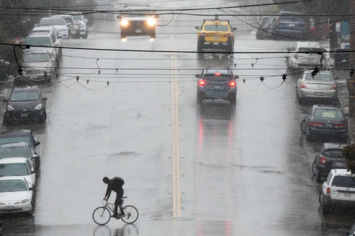 A bicyclist crosses a street during the rain storm in the Richmond District of San Francisco on November 17, 2020. The storm is the first strong storm of the season to hit the San Francisco Bay Area.