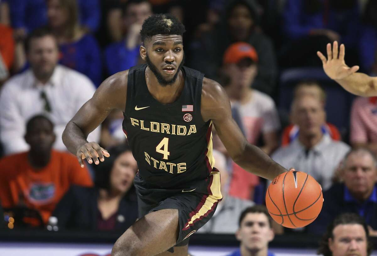 In this Nov. 10, 2019, file photo, Florida State forward Patrick Williams brings the ball up during the first half of the team's NCAA college basketball game against Florida in Gainesville, Fla. Williams is a potential lottery pick after being named the Atlantic Coast Conference's sixth man of the year last season. There is a report that the Spurs are looking to move up in the draft for Williams.