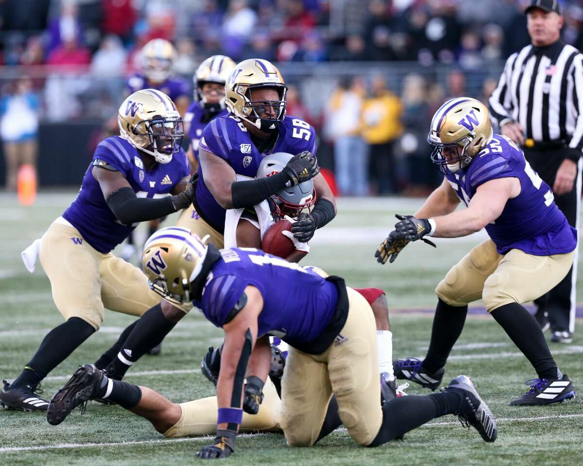 SEATTLE, WA - NOVEMBER 29: Washington's (58) Zion Tupuola-Fetui (OLB) and a slew of teammates tackle Washington State's (9) Renard Bell (WR) during the college football game between the Washington Huskies and the Washington State Cougars on November 29, 2019 at Husky Stadium in Seattle, WA. (Photo by Jesse Beals/Icon Sportswire via Getty Images)