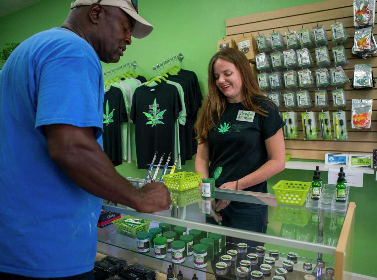 """Francis Jones smiles as he talks about his experience using CBD to manage knee and back pain with manager Caroline Mallon at Sacred Leaf, a store that specializes in selling products that contain CBD, in Katy. """"I haven't moved my knee like this in years,"""" said Jones, who said he has had four procedures on his knees and two on his back. Jones started using products containing CBD at the recommendation of a friend, and he said he's sleeping better and not experiencing the chronic pain that had previously plagued him. """"This stuff has changed my life,"""" said Jones. CBD provides many of the benefits of marijuana without the high and is legal in Texas."""