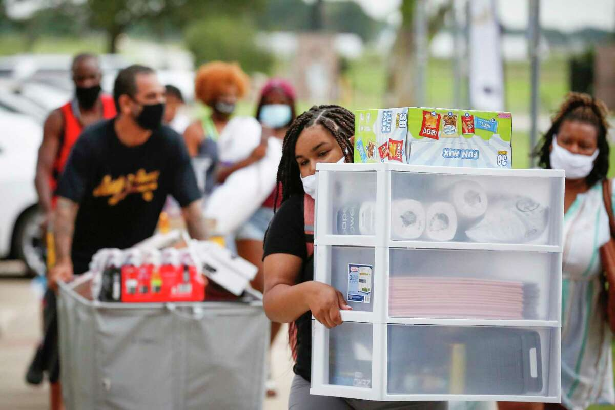 Freshman Nia Montgomery from Dallas, carries supplies for her room as she moved into Prairie View A&M University Monday, Aug. 17, 2020, in Prairie View.