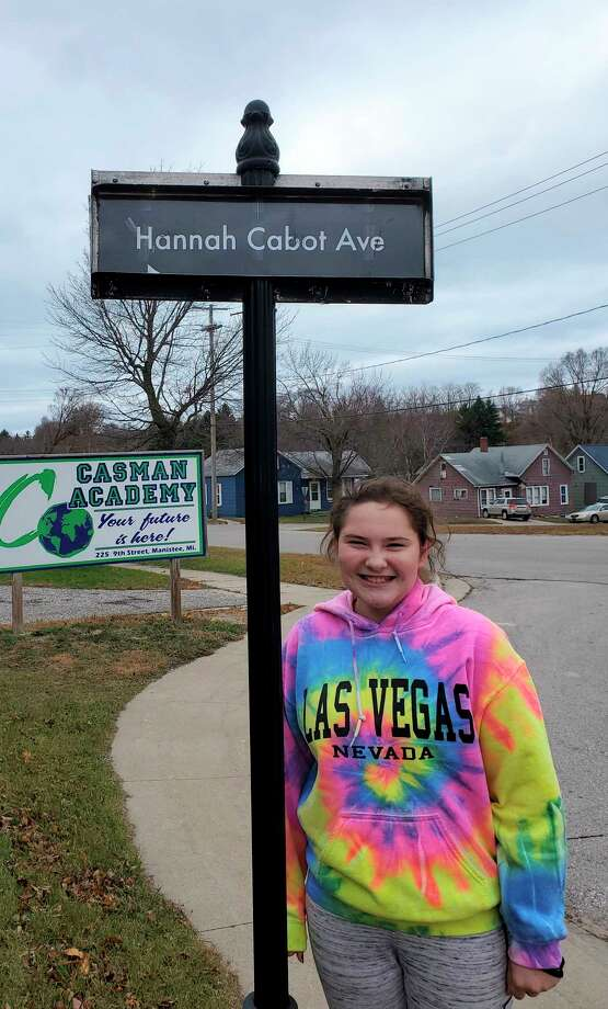 Hannah Cabot, the CASMAN Academy Student of the Month, poses next to the sign that names the school driveway in her honor. (Courtesy photo)