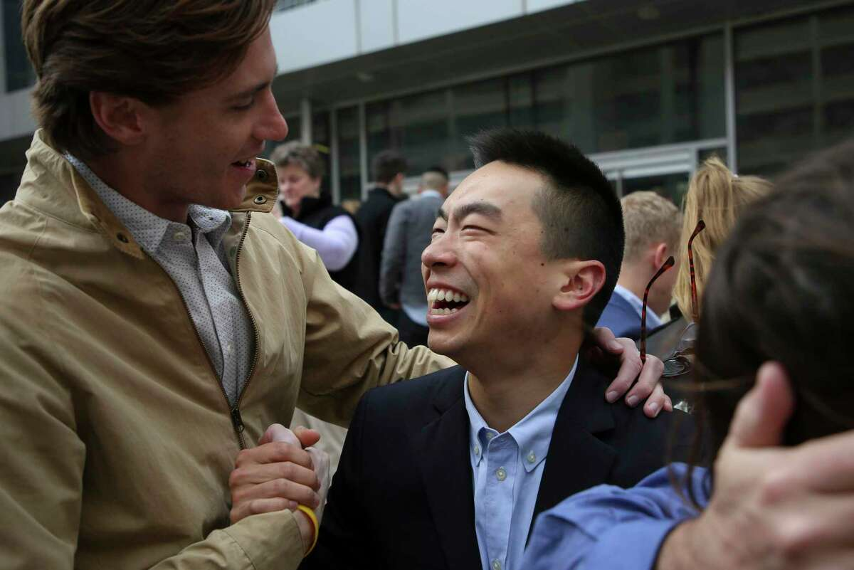In this March 15, 2019, file photo Baylor College of Medicine graduate Daniel Wang, center, is congratulated by his friend, Chris Ormiston, during Match Day in Houston.