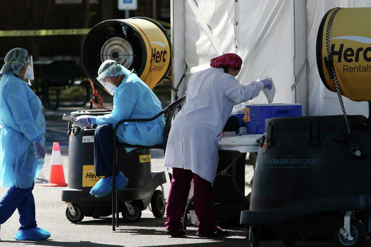 Workers prepare for patients at a COVID-19 drive through testing site in San Antonio on Monday.