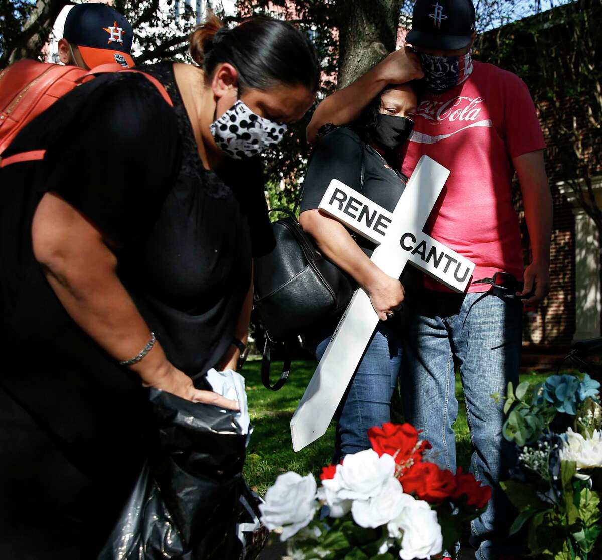 Michele Ramirez, from left, add flowers to a marker for Rene Cantu as Velinda Castillo is comforted by her husband Roland, where Cantu was killed while jogging on Montrose Blvd in Houston on Sunday, Nov. 15, 2020. Cantu was one of six people killed in Houston on Monday, November 9, 2020.