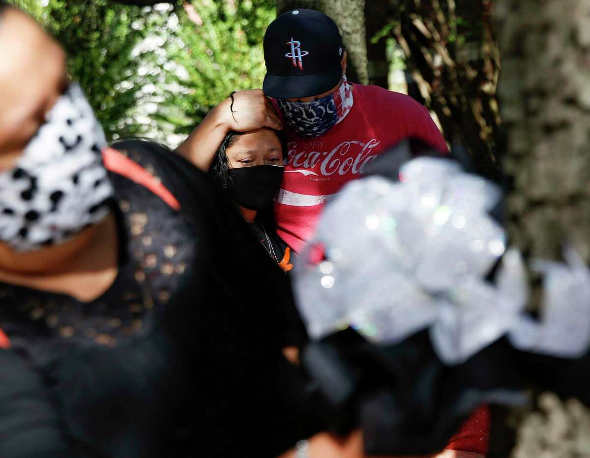 Roland Castillo comforts his wife, Velinda, as the rest of the family of Rene Cantu place a marker where he was recently killed while jogging on Montrose Blvd in Houston on Sunday, Nov. 15, 2020. Cantu was one of six people killed in Houston on Monday, November 9, 2020.