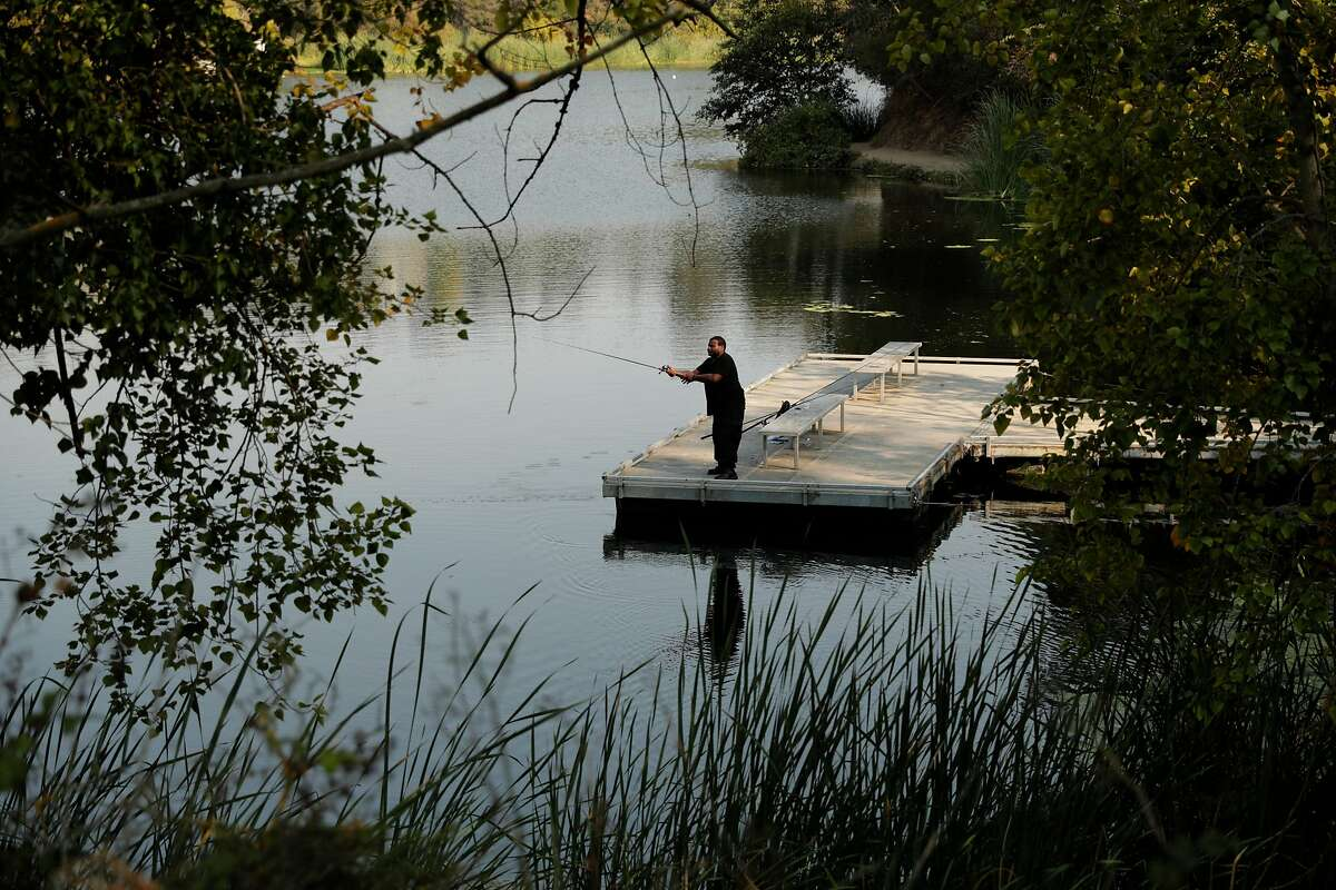 Donnell Pearson of Richmond fishing at Lake Temescal and trying to keep out of the intense heat in Oakland, Calif., on Monday, September 7, 2020. Temescal is among the local bodies of water which will be stocked with trout.