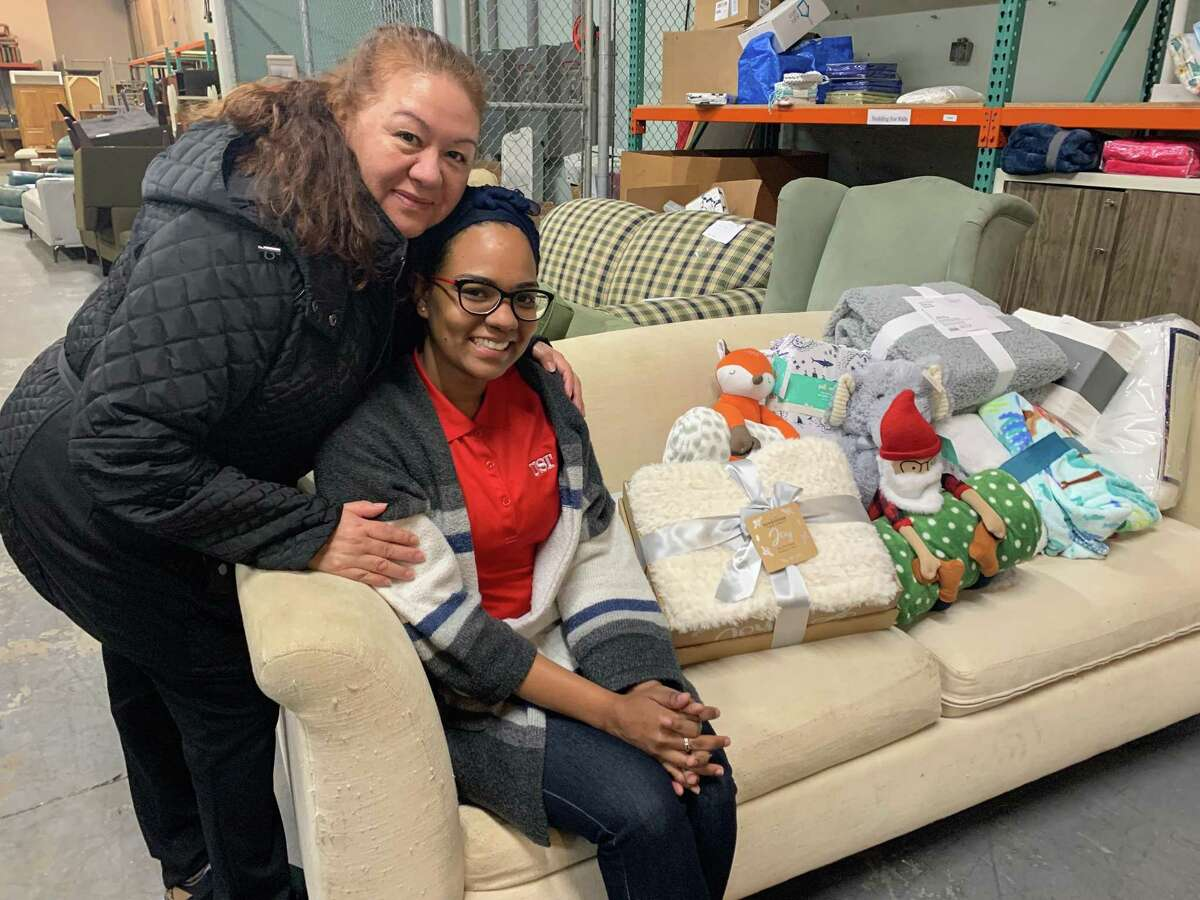 """Customers at the Houston Furniture Bank show off some of the donated blankets that are part of the """"No Kid On The Floor"""" bedding drive."""