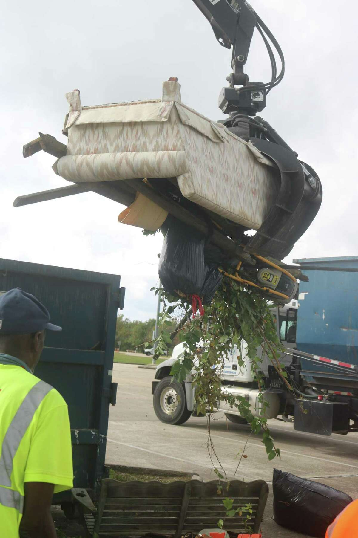 A couch and other debris is scooped up by the claw and placed in a dumpster during the city of Friendswood's annual Fall Haul.