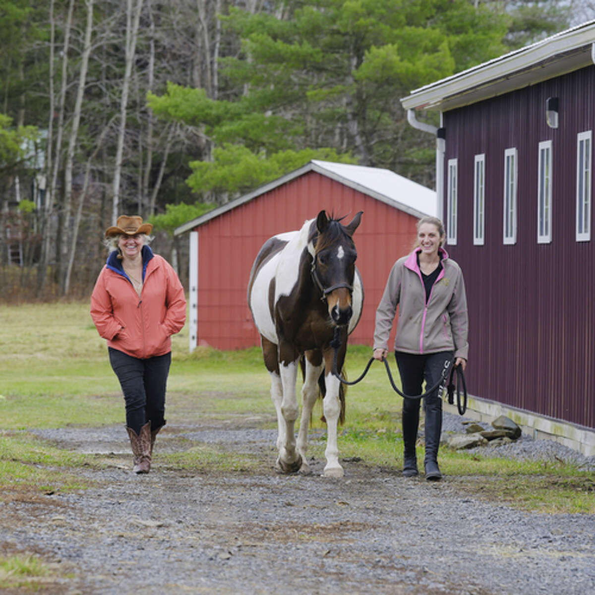 Kate Connor, left, owner of Cross Creek Equestrian Center, and her daughter, Emma Connor, owner of Topline Sporthorses, walk with Boomer at their horse farm on Thursday, Nov. 12, 2020, in Sloansville, N.Y. (Paul Buckowski/Times Union)