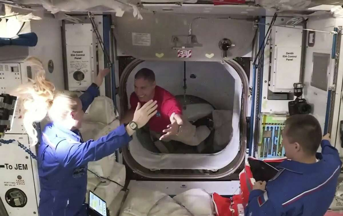 In this frame grab from NASA TV, astronaut Mike Hopkins, center, is greeted by astronaut Kate Rubins, left, as he enters the International Space Station from the vestibule between the SpaceX Dragon capsule and the ISS, early Tuesday, Nov. 17, 2020. At right is Expedition 64 commander Sergey Ryzhikov.