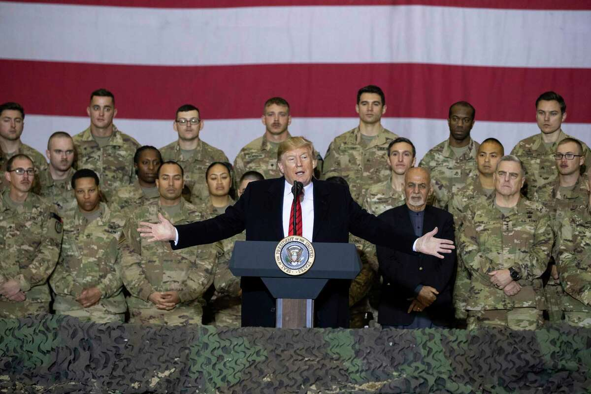 In this Nov. 28, 2019 file photo, President Donald Trump, center, with Afghan President Ashraf Ghani and Joint Chiefs Chairman Gen. Mark Milley, behind him at right, addresses members of the military during a surprise Thanksgiving Day visit at Bagram Air Field, Afghanistan.