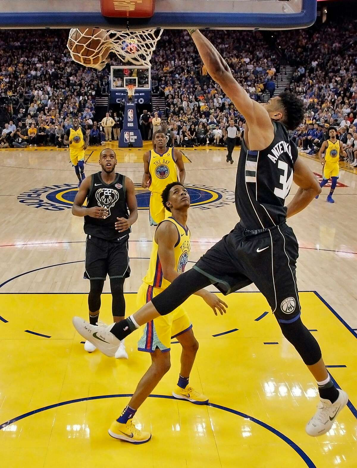 Giannis Antetokounmpo (34) dunks in the first half as the Golden State Warriors played the Milwaukee Bucks at Oracle Arena in Oakland, Calif., on Thursday, March 29, 2018.