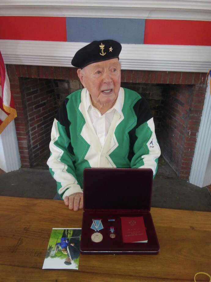 Trygve Hansen sits in the American Legion office with his medal and commendation from Russia while being interviewed via Zoom by a Russian media outlet. Photo: David Wold / Contributed Photo / Wilton Bulletin Contributed