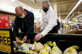 Mark Bristow, right, helps customer Jim Christman, left, choose a turkey at Jewel Osco on Friday, Nov. 6, 2020 in River Forest.  Bristow is the sales manager or meat and seafood.  (Stacey Wescott/Chicago Tribune/TNS)