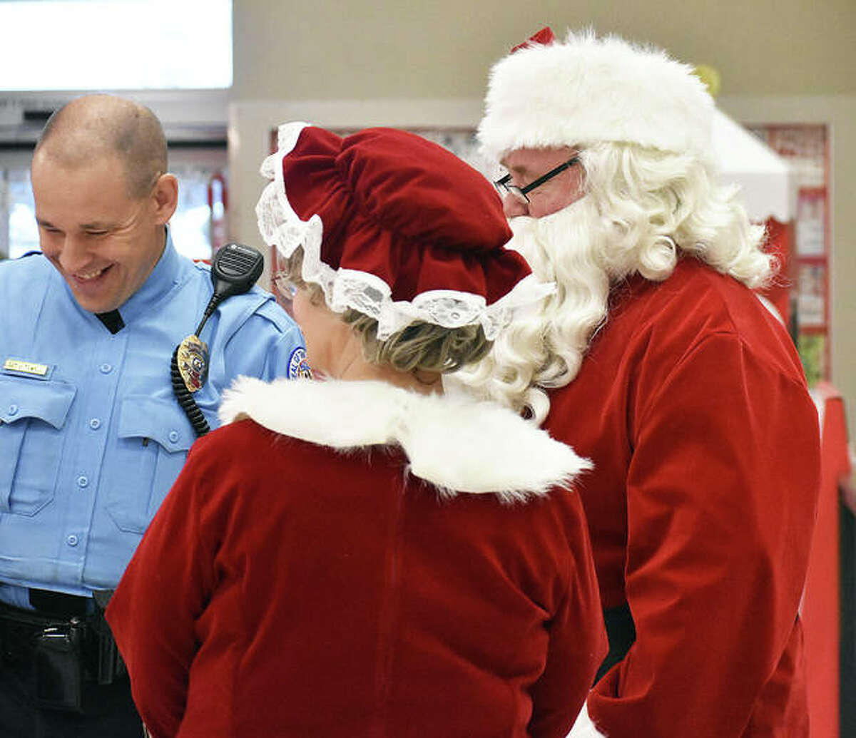 In this December 2018 file photo, an Edwardsville Police officer, left, jokes with Santa and Mrs. Claus at Target during the annual
