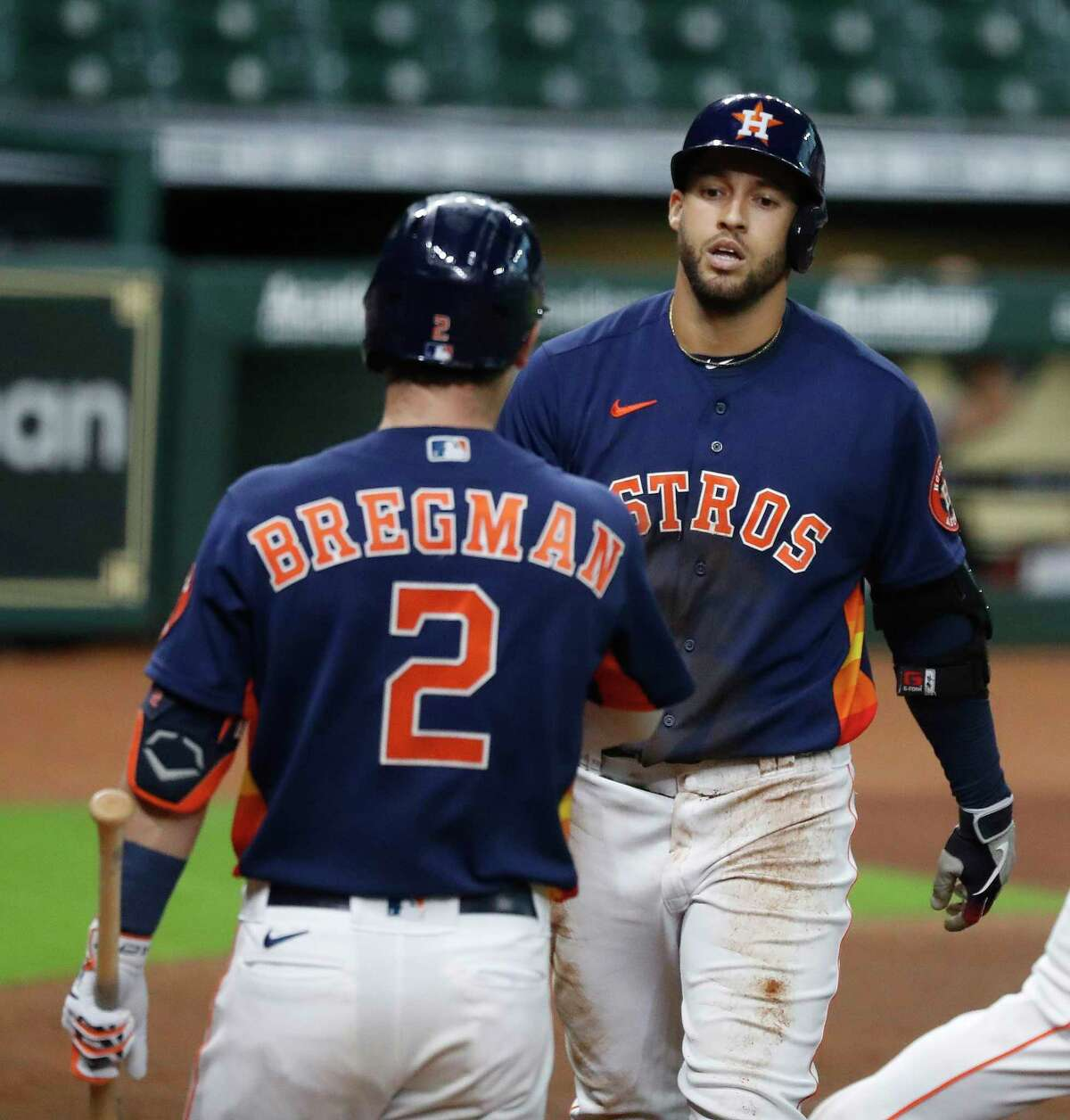 Houston Astros George Springer (4) celebrates with Alex Bregman (2) after hitting an inside-the-park home run on a fly ball to center field during the sixth inning of an MLB baseball game at Minute Maid Park, Sunday, September 20, 2020, in Houston.