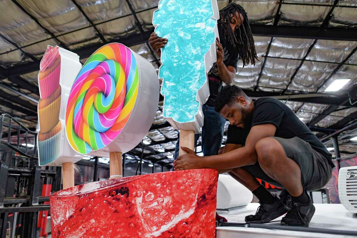 Workers place pieces of the 3-D signage on the Stir Soda mobile food truck.
