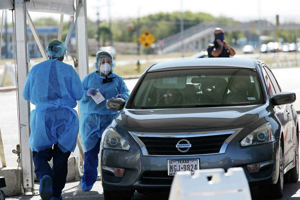 Personnel prepare to test a woman at a COVID-19 drive through testing site at a CentroMed Clinic on Palo Alto Road, Monday, Nov. 16, 2020.