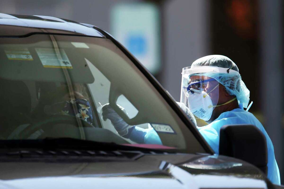 Personnel test a person at a COVID-19 drive through testing site at a CentroMed Clinic on Palo Alto Road, Monday, Nov. 16, 2020.