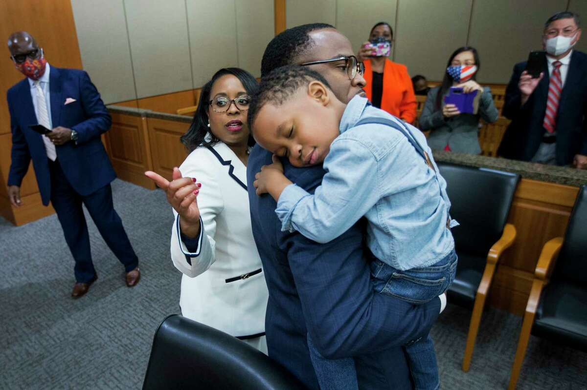 Josiah Babalola, 4, lays his head on the shoulder of his father, Samson, after his mother, Teneshia Hudspeth, left, was sworn in as the new Harris County Clerk Tuesday, Nov. 17, 2020 in Houston. Hudspeth is Harris County's first African American county clerk.
