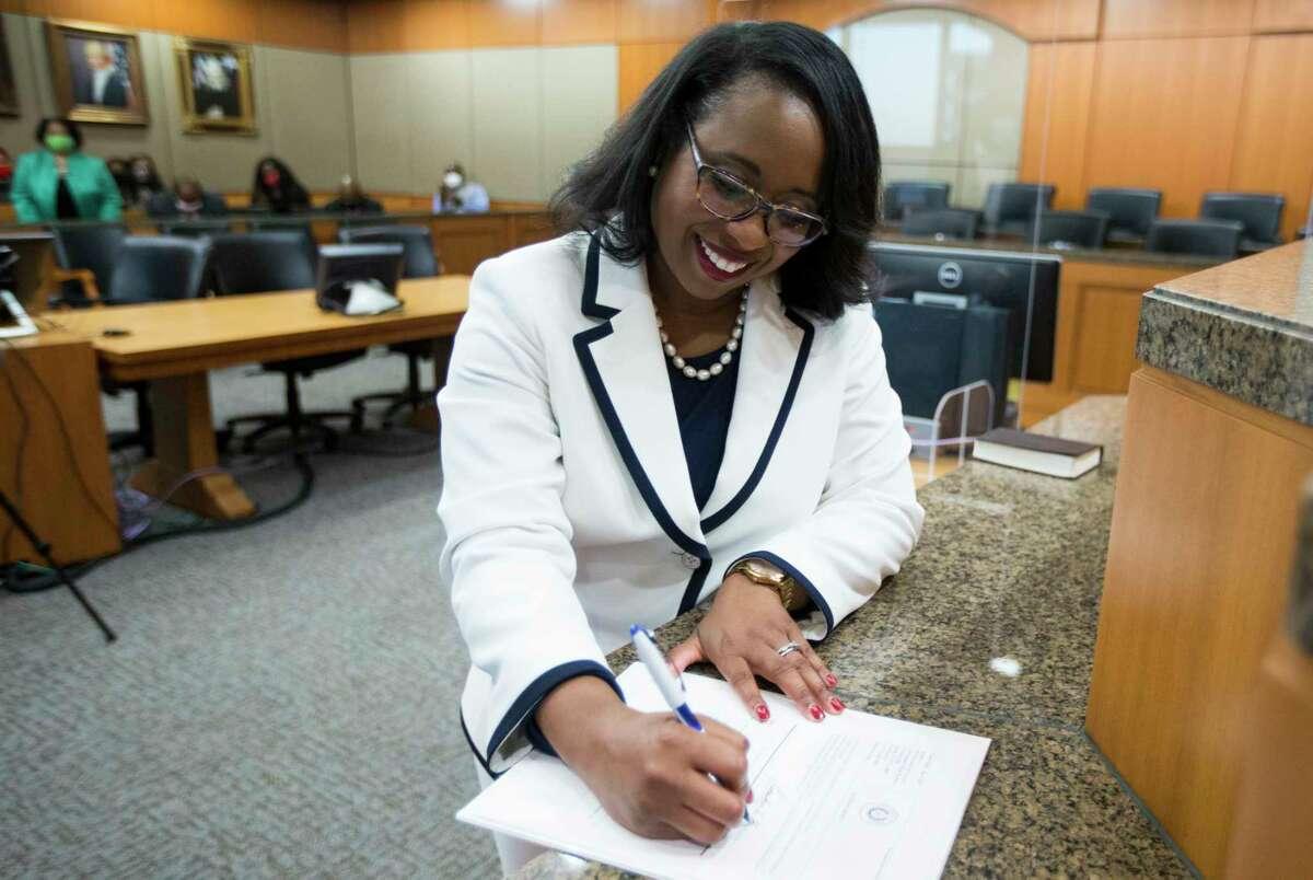 Teneshia Hudspeth signs paperwork after she was sworn in as the new Harris County Clerk Tuesday, Nov. 17, 2020 in Houston. Hudspeth is Harris County's first African American county clerk.