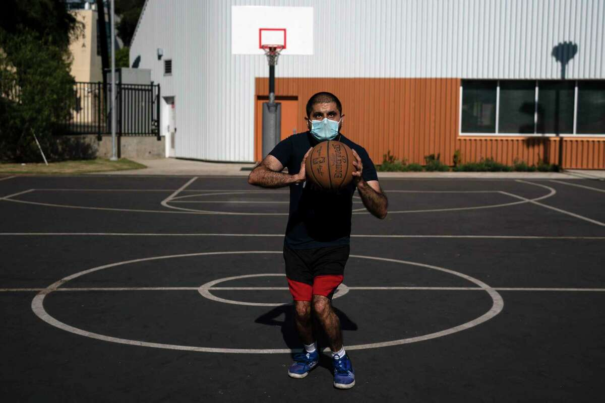 Kousha Vedadi, 31, plays basketball with his mask on in Los Angeles, Tuesday, Nov. 17, 2020. California Gov. Gavin Newsom said he was strengthening a mask requirement outside of homes with limited exceptions. (AP Photo/Jae C. Hong)