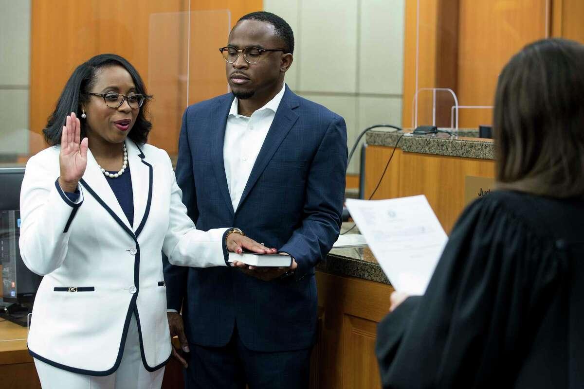 Teneshia Hudspeth stands with her husband, Samson Babalola, as she is sworn in Tuesday as the new Harris County clerk by Judge Lesley Briones. Hudspeth is Harris County's first African American county clerk.