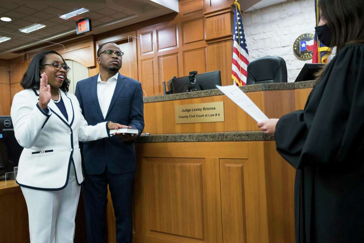 Teneshia Hudspeth stands with her husband, Samson Babalola, as she is sworn in as the new Harris County Clerk, by Judge Lesley Briones Tuesday, Nov. 17, 2020 in Houston. Hudspeth is Harris County's first African American county clerk.