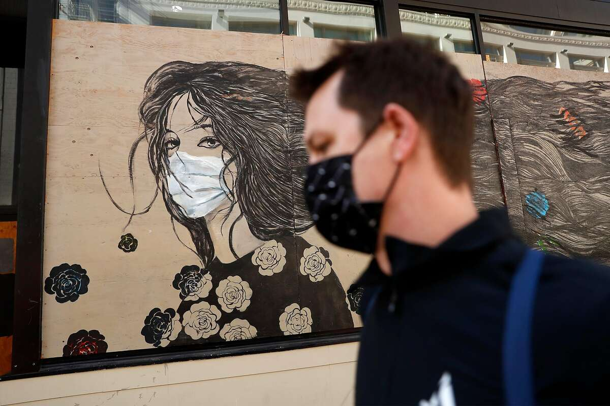A masked pedestrian passes a mural by Farnaz Zabetian on the Powell Street Walgreen's in San Francisco, Calif., on Thursday, November 12, 2020. California is expected to hit 1 million COVID cases on Thursday as the pandemic continues practically unabated across the country.