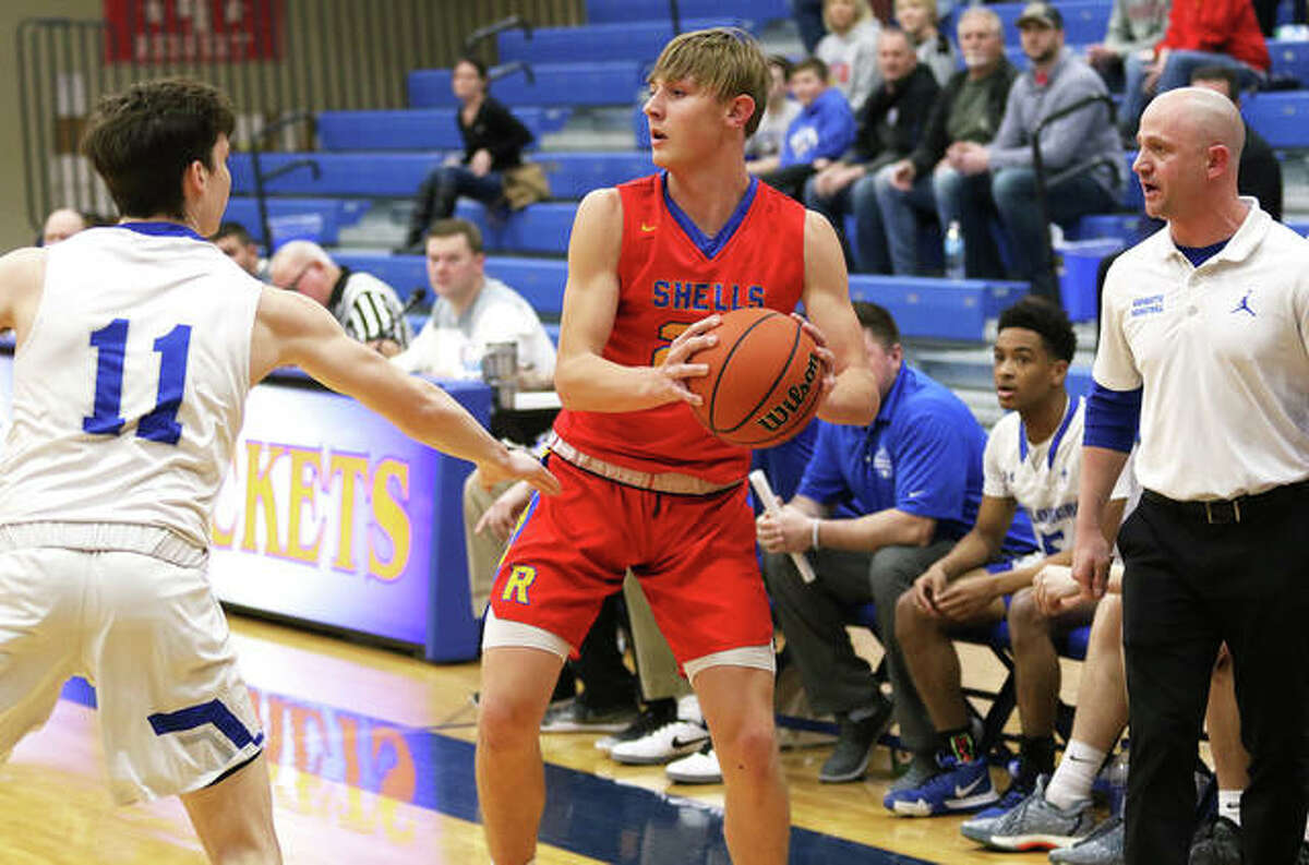 Roxana's Gavin Huffman (in red), looks for a teammate while in action last season against Marquette Catholic. Explorers coach Steve Medford is at right. The IHSA announced Tuesday that the start of winter sports, including basketball, is on hold following the announcement by Gov. JB Pritzker that the state will move to Tier 3 mitigations on Friday as a result of the COVID-19 pandemic.