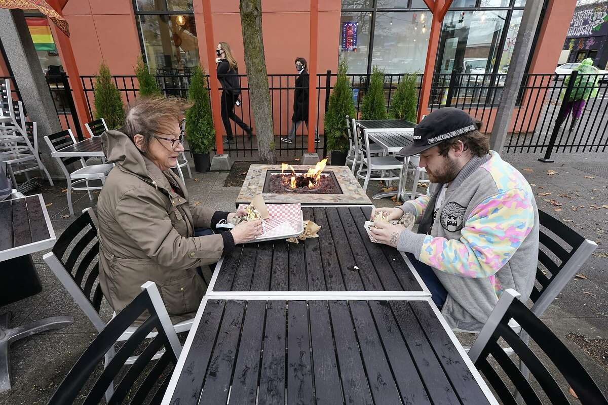 Diners Bonnie Breitman, left, and Casey McGan huddle near an outdoor gas fire as they eat lunch outside in a blustery wind Tuesday, Nov. 17, 2020, in Bellingham, Wash. Washington Gov. Jay Inslee on Sunday announced tighter restrictions in the state in response to a flood of new cases of COVID-19, the disease caused by the coronavirus. Restaurants and bars will again be limited to outdoor dining and to-go service, gyms, and some entertainment centers will be required to close indoor services. Retail stores, including grocery stores, will be ordered to limit indoor capacity and indoor social gatherings will be prohibited unless attendees have quarantined for 14 days or tested negative for COVID-19 and quarantined for a week. (AP Photo/Elaine Thompson)