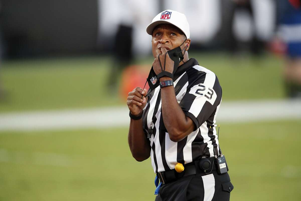 NFL referee Jerome Boger (23) adjust his mask during an NFL football game between Green Bay Packers and the Tampa Bay Buccaneers Sunday, Oct. 18, 2020, in Tampa, Fla. (Jeff Haynes/AP Images for Panini)
